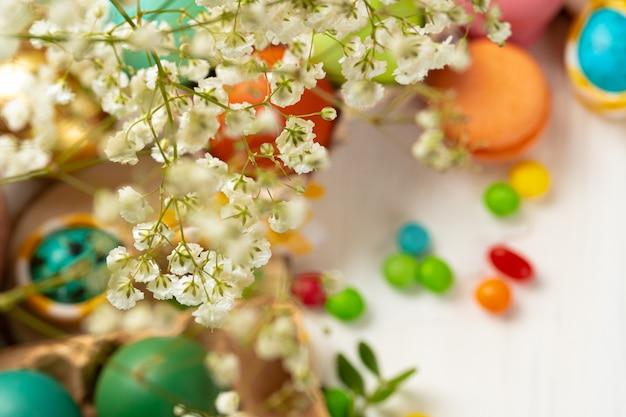 Colofrul wielkanocni jajka i rozrzuceni cukierki na drewnianym stole