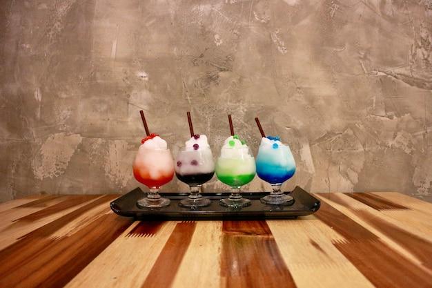 Colourful lodowy owocowy smoothie w małym szkle jest na drewnianym stole.