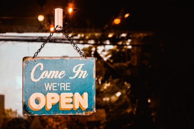 Come in jesteśmy otwarty znak na drzwiach kawiarni.