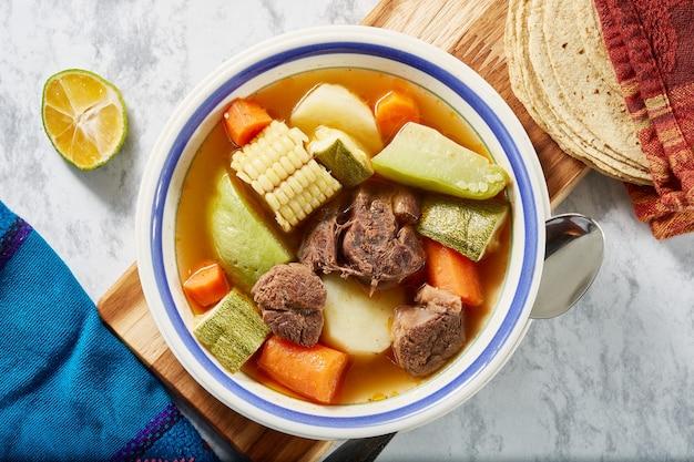Comida mexicana caldo de res rojo o mole de olla con verduras y tortillas de maiz