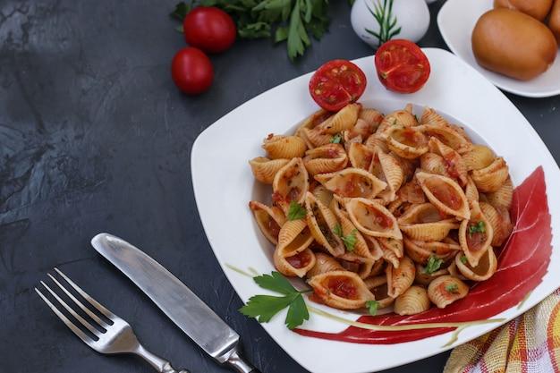 Conchiglie włoskie skorupy makaronu z pomidorami koktajlowymi i sosem pomidorowym na ciemnym tle
