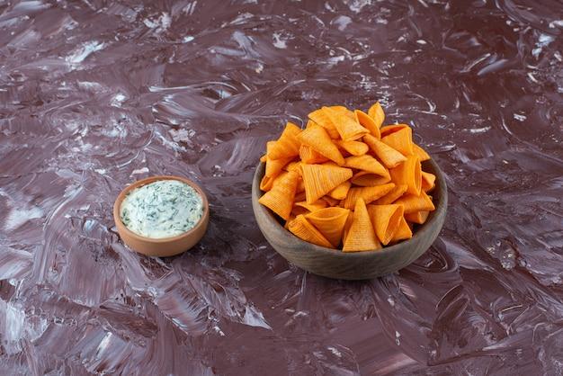 Cone chips w misce z jogurtem w misce na marmurowej powierzchni