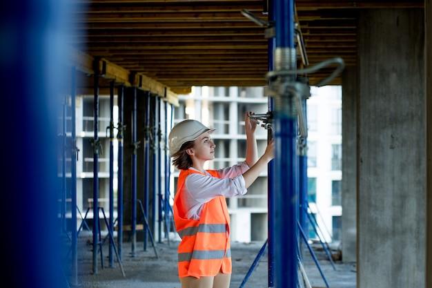 Confident kobieta budowlana sprawdza mocowania na monolitycznej konstrukcji. koncepcja budowy.