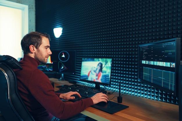 Confident man video editor współpracuje z materiałami wideo w creative office studio.
