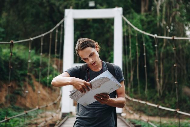 Confused caucasion człowiek patrząc na mapę podróży i odkrywania pojęcia