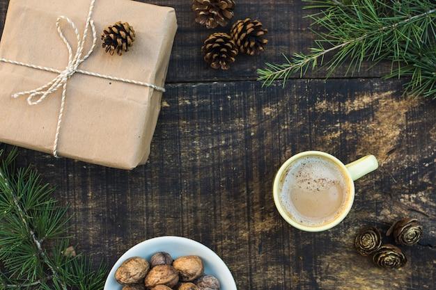 Conifer stożki i gałęzie w pobliżu kawy i prezent