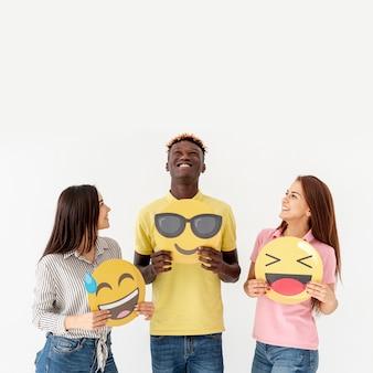 Copy-space młodzi przyjaciele trzyma emoji