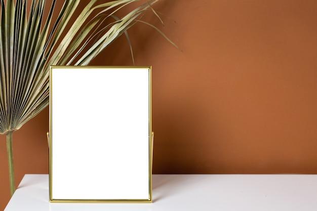 Copyspace złota rama i roślin na białym stole z ciemnopomarańczowym tłem ściany