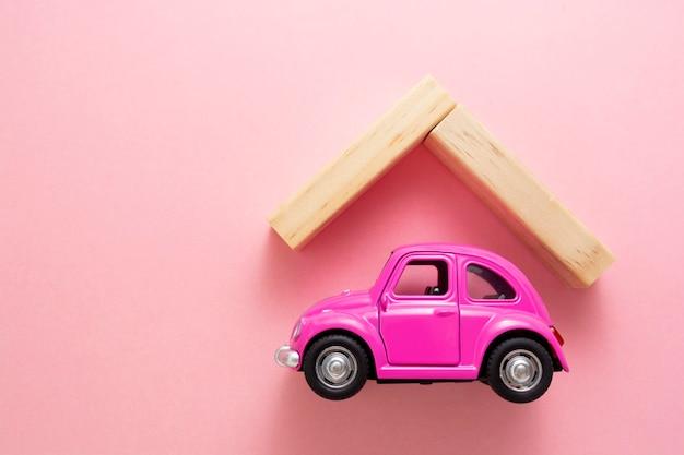 Corby, wielka brytania - 02. 02. 2021. koncepcja ubezpieczenia samochodu różowy model samochodu i drewniany dach na różowym tle