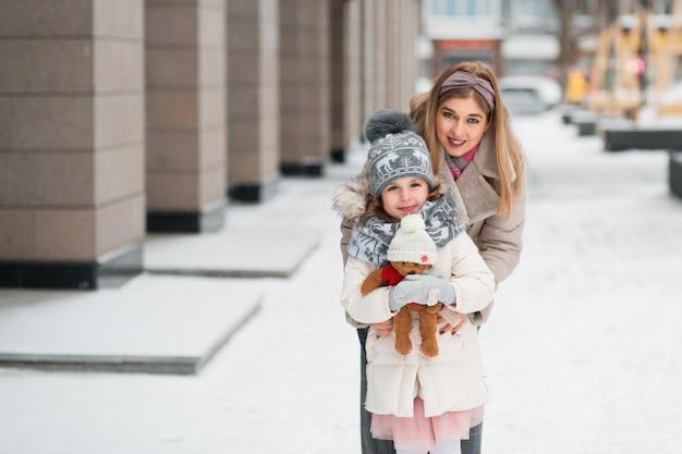 Córeczka przytulanie z matką i trzymając misia w zimowym mieście