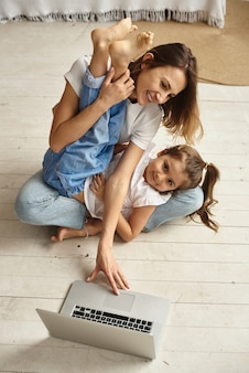 Córka bawi się z mamą i kotem, podczas gdy mama pracuje na komputerze