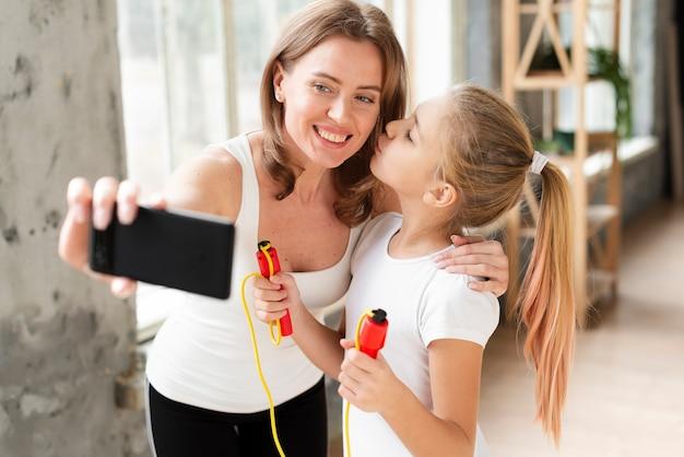 Córka całuje matkę biorąc selfie