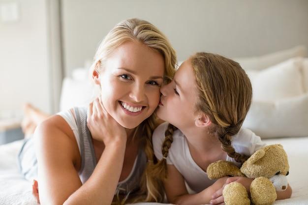Córka całuje matkę w policzek w sypialni