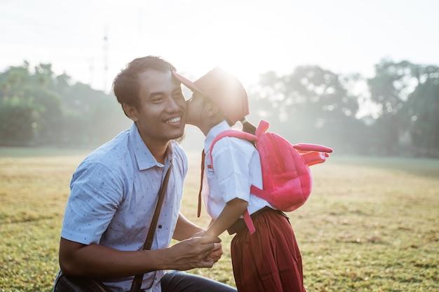 Córka całuje ojca w policzek pierwszego dnia szkoły podstawowej primary