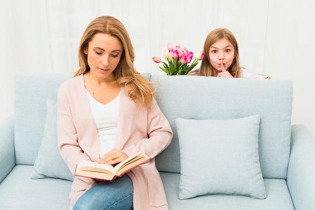 Córka chowa się za kanapą z matką