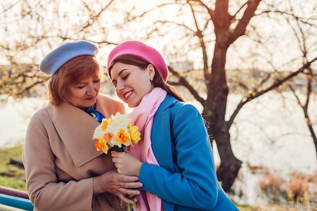 Córka, dając jej starszy matka bukiet kwiatów nad rzeką wiosną