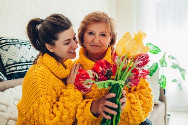 Córka daje mamie w domu bukiet kwiatów na dzień matki, ubrana w podobne swetry
