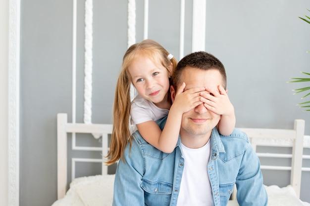 Córka dziewczyny bawi się z tatą w domu zamykając oczy, szczęśliwa rodzina