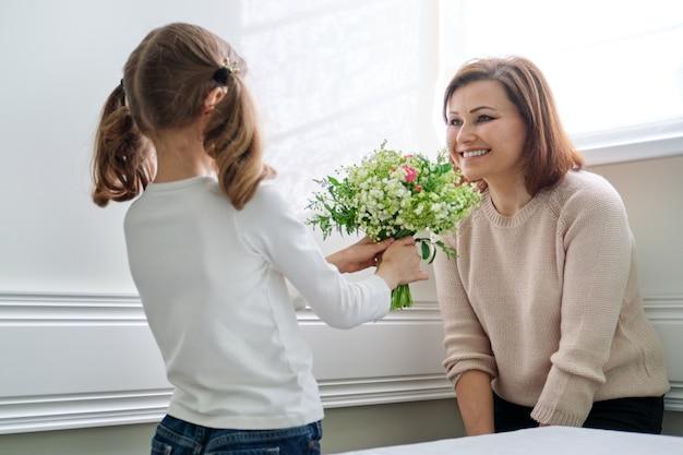 Córka gratuluje mamie pięknych wiosennych kwiatów na dzień matki