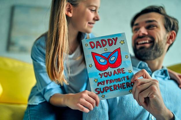 Córka gratuluje ojcu i wręcza mu pocztówkę z okazji dnia szczęśliwego ojca!