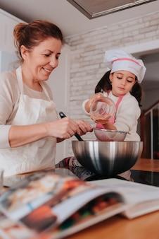 Córka i mama gotują w domu pyszny deser na dzień matki. kuchnia rustykalna i przytulna. szczęśliwa matka i córka. pionowy.