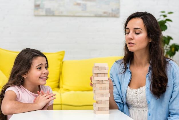 Córka i matka grając w drewnianą wieżę