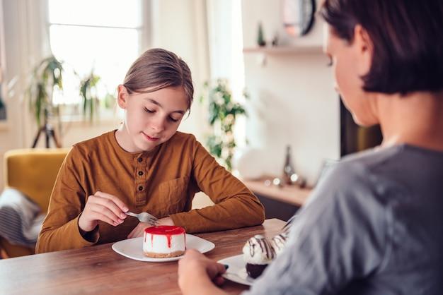 Córka i matka jedzenie ciasta w domu