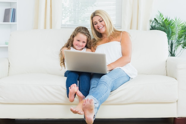 Córka i matka odpoczywa na kanapie z laptopem