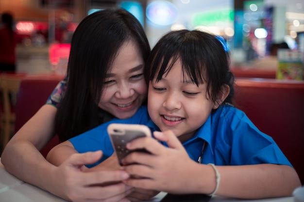 Córka i matka patrząc na smartfona z uśmiechem i radością