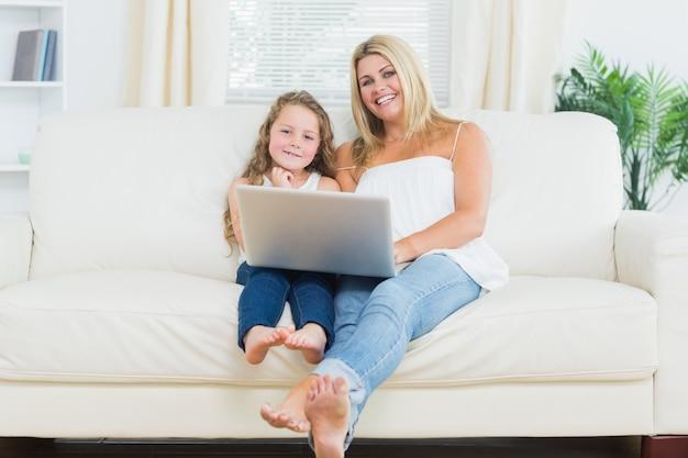 Córka i matka relaksuje na kanapie z notatnikiem