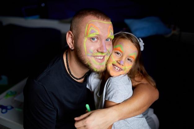 Córka i ojciec malują twarz, dobrze się bawią
