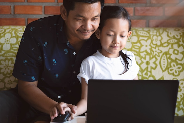 Córka i ojciec uczy się i bawić się komputerowego laptop w domu