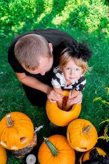 Córka i ojciec wyciągają nasiona i włóknisty materiał z dyni przed rzeźbieniem na halloween. przygotowuje latarnię z dyni. dekoracja na imprezę. szczęśliwa rodzina. mały pomocnik. widok z góry.