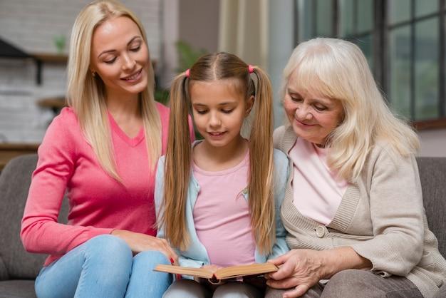 Córka i rodzina siedzą na kanapie i czytają książkę