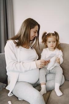 Córka kobieta w ciąży w jasne ubrania, siedząc na kanapie.
