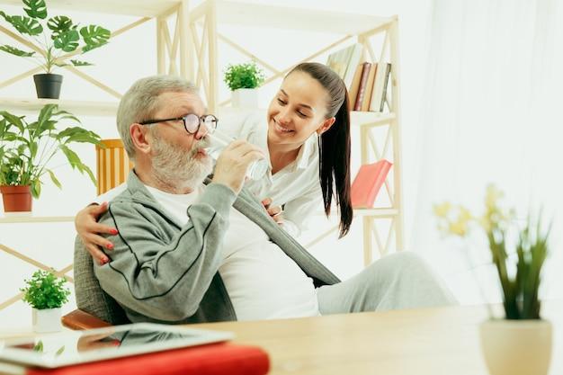 Córka lub wnuczka spędza czas z dziadkiem lub starszym mężczyzną pijąc wodę. dzień rodziny lub ojca, emocje i szczęście. portret styl życia w domu. dziewczyna dba o tatę.