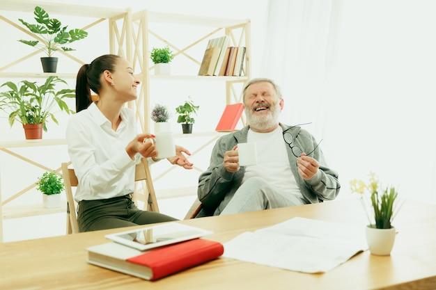 Córka lub wnuczka spędza czas z dziadkiem lub starszym mężczyzną przy herbacie
