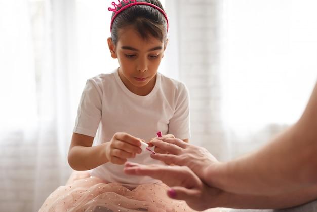 Córka maluje tatusiami paznokcie.