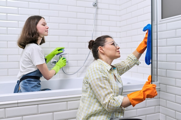 Córka matka i nastolatek razem sprzątanie w łazience. dziewczyna pomaga matce sprzątać w domu. nastolatki i rodzice, relacje, czystość i sprzątanie, obowiązki domowe