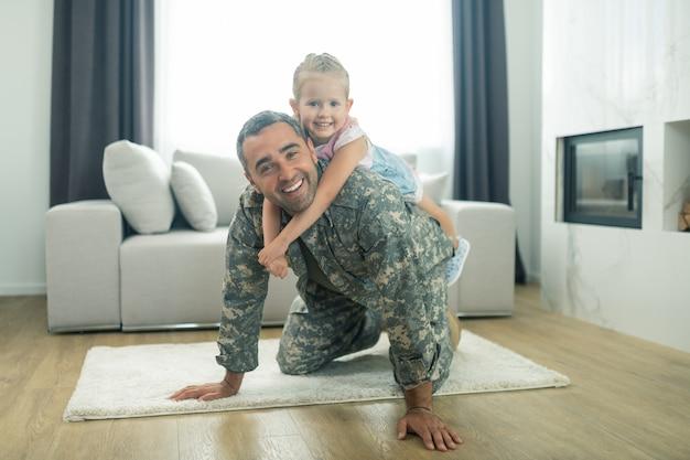 Córka na plecach. urocza promieniejąca dziewczyna siedzi na plecach ojca, czując się szczęśliwa i niezapomniana