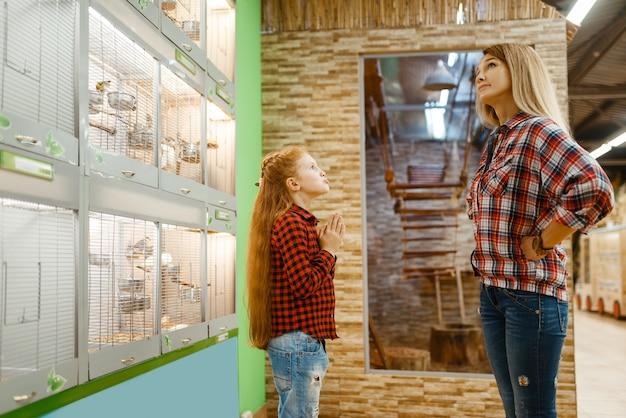 Córka namawia matkę, żeby kupiła ptaka w sklepie zoologicznym. kobieta i małe dziecko kupują sprzęt w sklepie zoologicznym, akcesoria dla zwierząt domowych