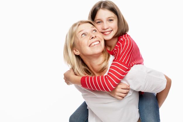 Córka nastolatka i matka śmieją się i przytulają. miłość i wsparcie w relacjach rodzinnych. biała ściana. miejsce na tekst.