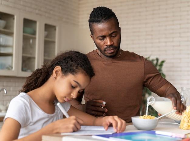 Córka odrabia lekcje obok ojca w kuchni