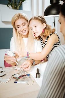 Córka pomaga. córka ubrana w różowe kolczyki i bransoletki pomaga mamie w doborze koloru paznokci