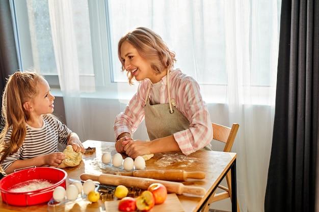 Córka pomaga mamie w wyrabianiu ciasta w nowoczesnej kuchni