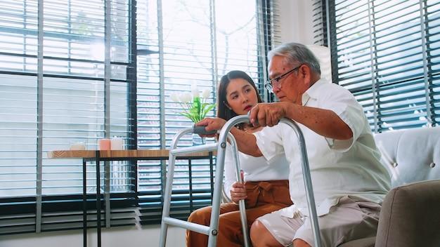 Córka pomaga niepełnosprawnemu ojcu w nauce chodzenia z balkonikiem w domu.