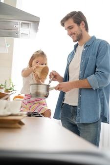 Córka pomaga ojcu gotować posiłek w kuchni.