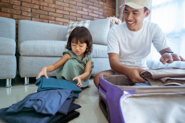 Córka pomaga ojcu włożyć ubrania do walizki