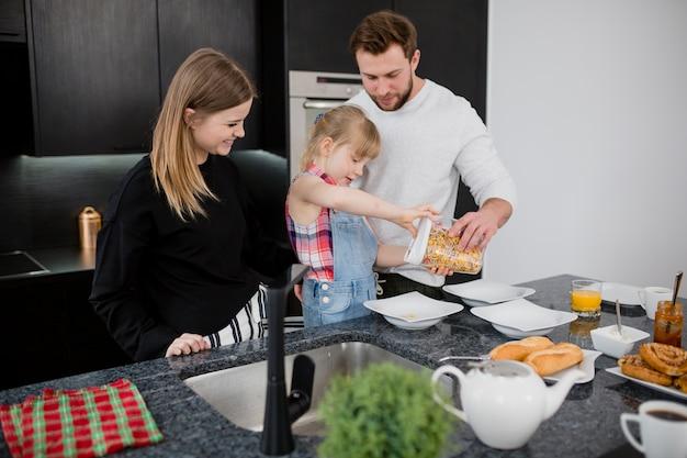 Córka pomaga rodzicom przygotowywać śniadanie