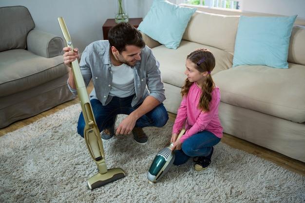 Córka pomagająca ojcu w czyszczeniu dywanu odkurzaczem